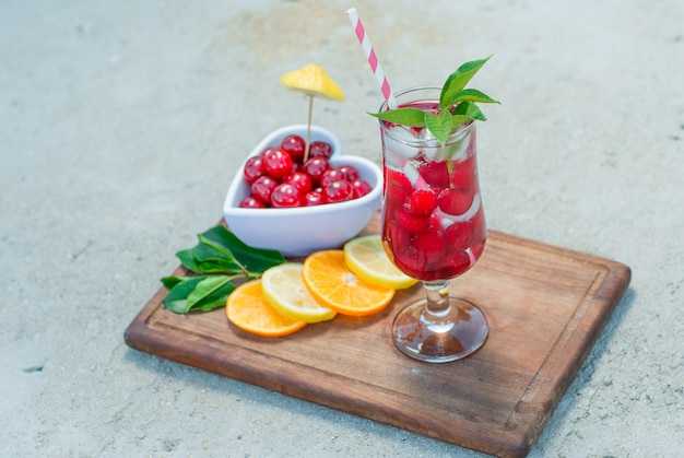Icy drink in a glass with cherries, lemon, leaves close-up on cement and cutting board