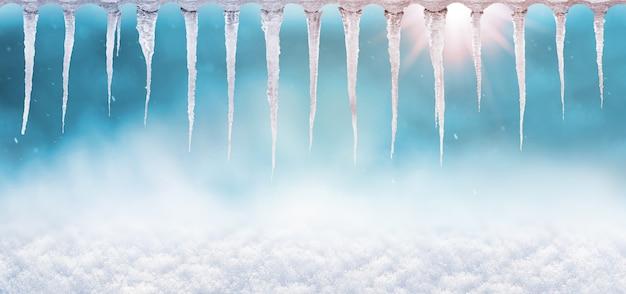 ぼやけた背景の太陽の下で氷のつらら