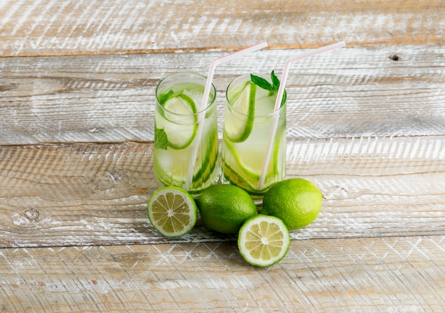Icy lemonade in glasses with lemon, basil flat lay on a wooden