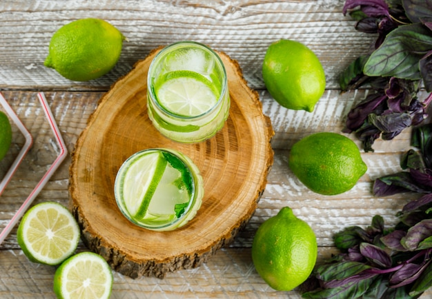 Limonata ghiacciata con limoni, basilico, cannucce in bicchieri su legno e tagliere, vista dall'alto.