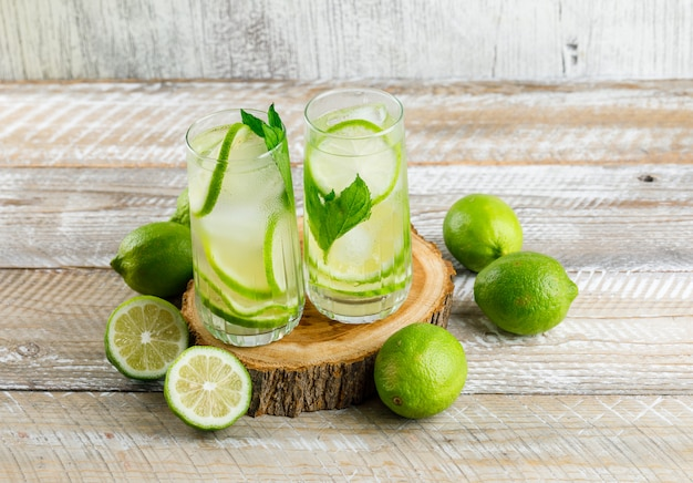 Icy lemonade with lemons, basil, wood in glasses on wooden and grungy, high angle view.
