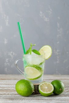 Icy mojito cocktail in a cup with limes, mint, straw side view on wooden and plaster wall