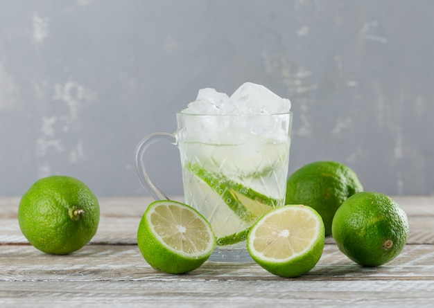 Icy mojito cocktail in a cup with limes side view on wooden and plaster background