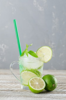 Icy mojito cocktail in a cup with limes, straw, mint side view on wooden and plaster background