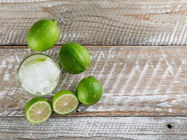 Icy mojito cocktail in a glass cup with limes flat lay on a wooden surface