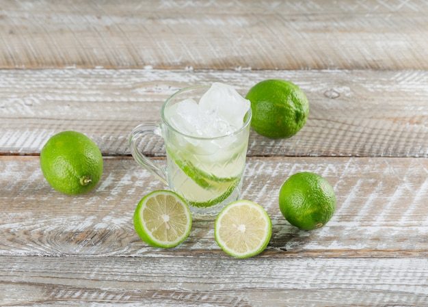 Icy mojito cocktail with limes in a cup on wooden surface, high angle view.