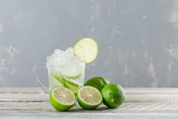 Icy mojito cocktail with limes in a glass cup on wooden and plaster background, side view.