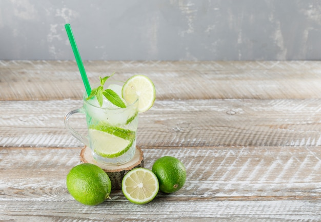 Icy mojito cocktail with limes, mint straw in a cup on wooden and plaster background, high angle view.