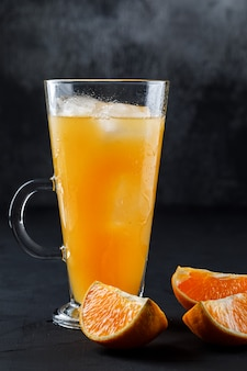 Icy orange juce in a glass cup with orange slices