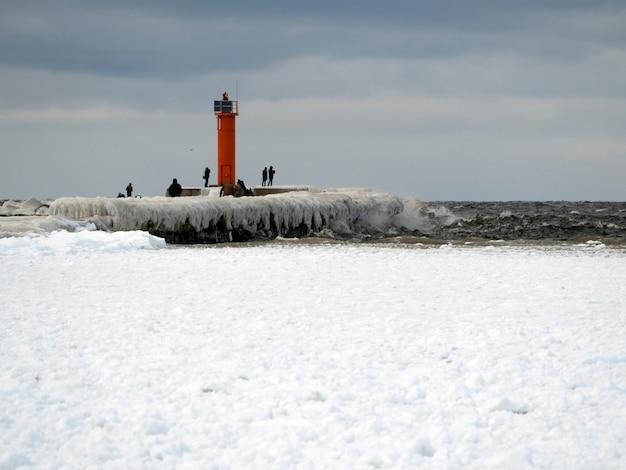 등대와 얼음 부두. 사람들은 멀리서 걷습니다.