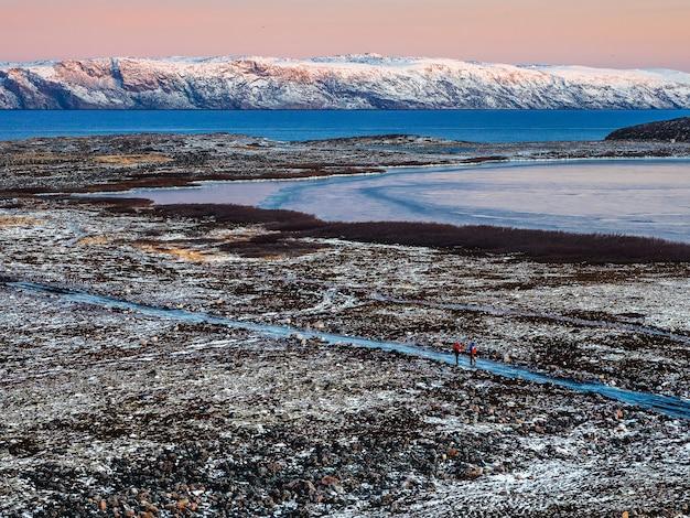 ツンドラを通る氷のように滑りやすい北極の道。バレンツ海の素晴らしい山の風景。チェベルカ。