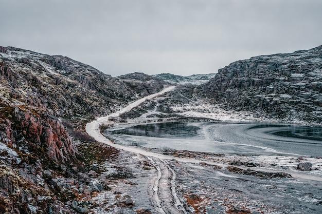Teriberka의 툰드라 언덕을 통과하는 얼음 겨울 도로. 놀라운 다채로운 북극 풍경.