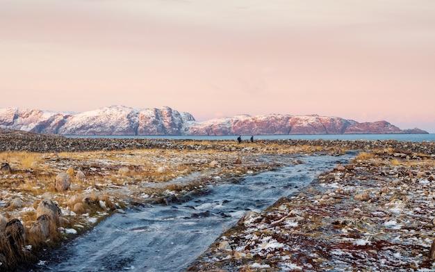Ледяная зимняя дорога через холмы тундры в териберке. прекрасный панорамный горный пейзаж с тундрой на берегу баренцева моря. териберка.