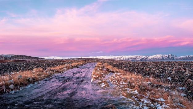 テリベルカのツンドラを通る氷のような冬の道。驚くほどカラフルな北極の風景。