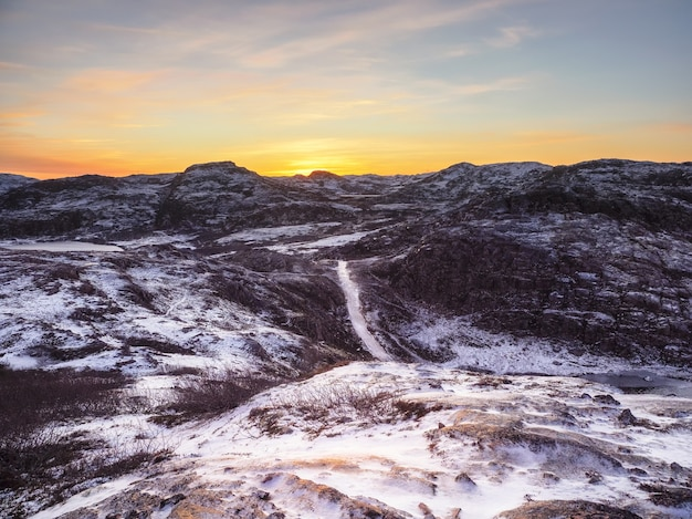 Icy winter road through the tundra hills northern wildlife