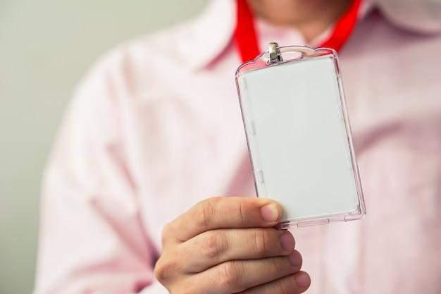 彼の手でidカードを保持している男