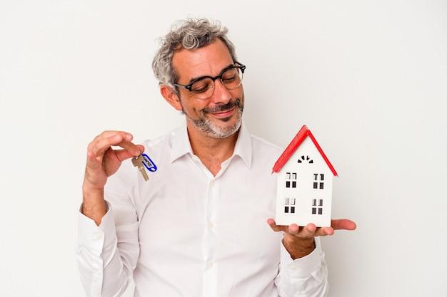 青い背景で隔離の鍵とおもちゃの家を保持しているアイドル時代のビジネスマン