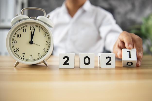 아이디어 및 사업 계획 시간 개념, 사업가는 2020 년에서 2021 년까지 큐브 번호를 나무 테이블에 놓습니다.
