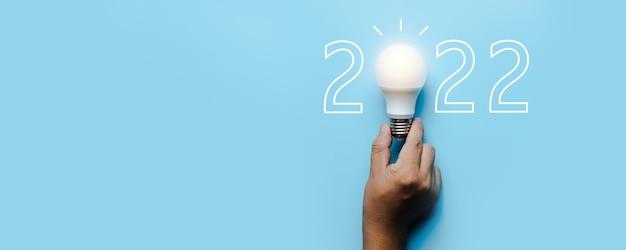 2022年のアイデアと創造性、青い背景に新年番号の電球
