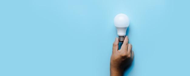 青い背景の上のアイデアと創造的な革新の電球
