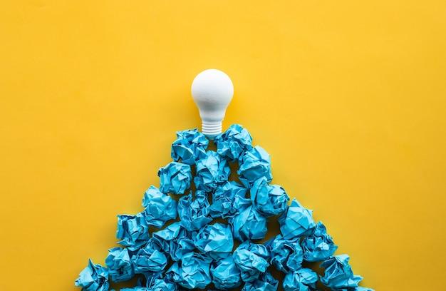 山の形をした紙のしわくちゃのボールの上に電球を使ったアイデアと創造性の概念