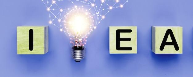 アイデアと新しい創造的思考の概念、青い背景の木製ブロックにアイデアの言葉と電球