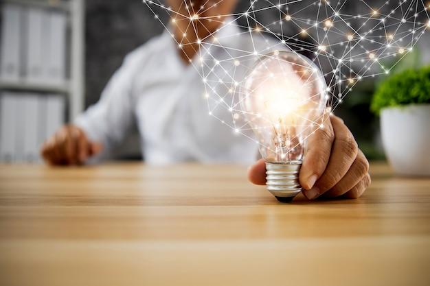 Идея и концепция технологических инноваций, бизнесмен, держащий лампочку, сияющую с линией подключения питания