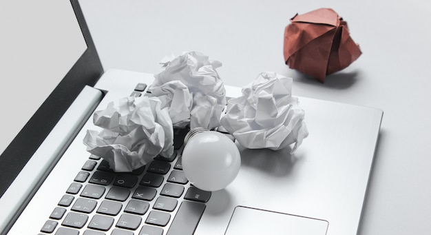 Idea business concept. laptop, crumpled paper balls, led light bulb on gray table
