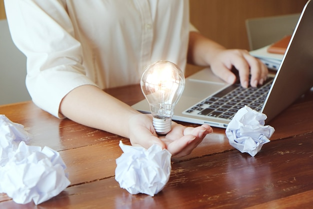Idea of business person holding light bulb concept creativity with bulbs.
