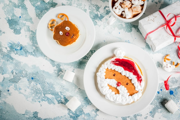 Idea for a children's christmas breakfast: pancakes decorated like santa claus and deer, cocoa with teddy bears and deer marshmallow. on a light surface, with xmas gift top view copy space