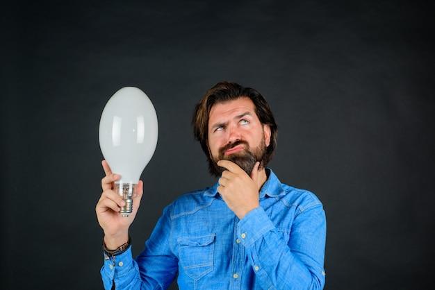 手にアイデアコンセプトランプ電球を持つ良いアイデア物思いにふける男アイデアの誕生に驚いた男