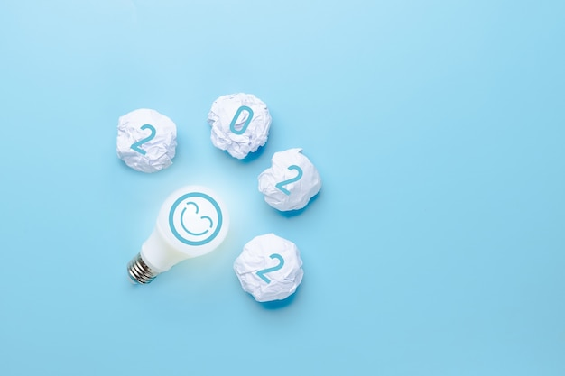 Idea and creative in 2022, lighting bulb with new year number on blue background