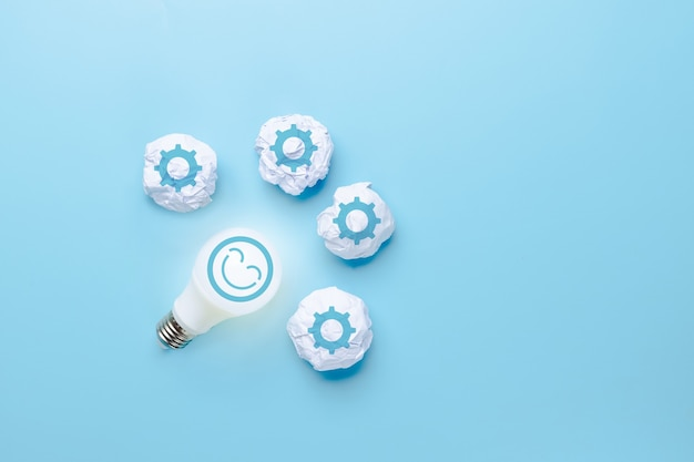 Idea and creative innovation with face smile icon and light bulb and waste paper of work icon on blue background