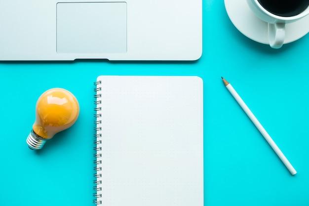전구 메모장과 컴퓨터 노트북을 사용한 아이디어 창의성 개념