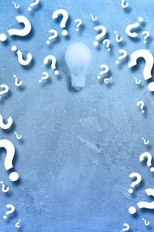 Idea of a glowing light bulb a lot of questions symbols