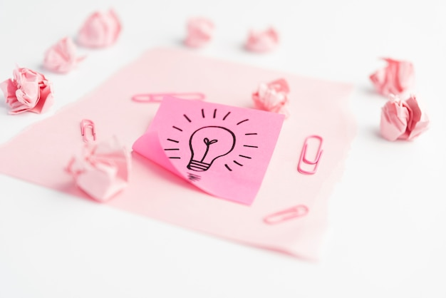 Idea icon on adhesive note with paperclip; crumpled paper and card paper over white desk