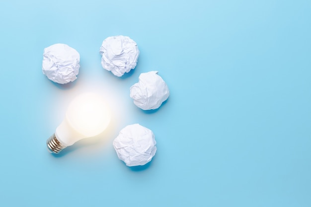 Idea and innovation with save of world concept, light bulb lighting with waste paper on blue background