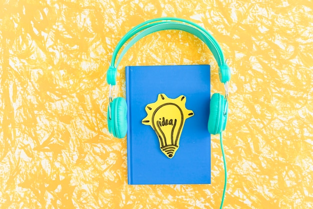 Idea light bulb on blue cover notebook with headphone on yellow backdrop