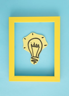 Idea light bulb inside the yellow frame on blue background