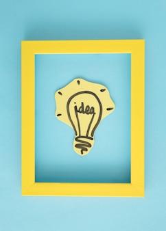 青い背景に黄色い枠の中のアイデア電球