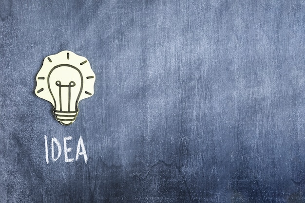 Idea light bulb paper cutout on chalkboard