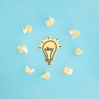 Idea light bulb surrounded with crumpled paper on blue background
