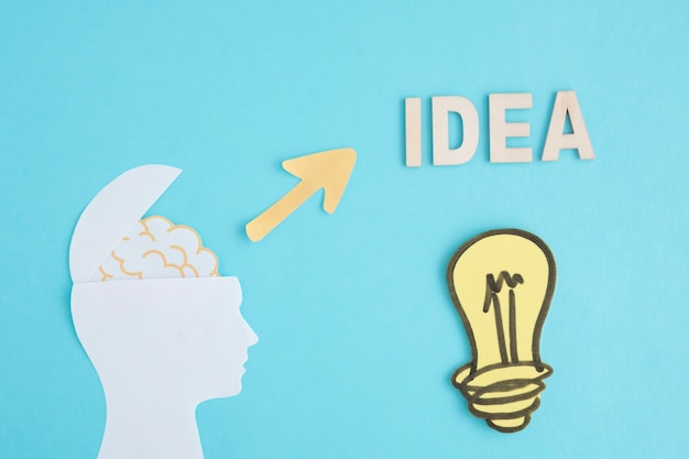Idea light bulb with open brain head on blue background