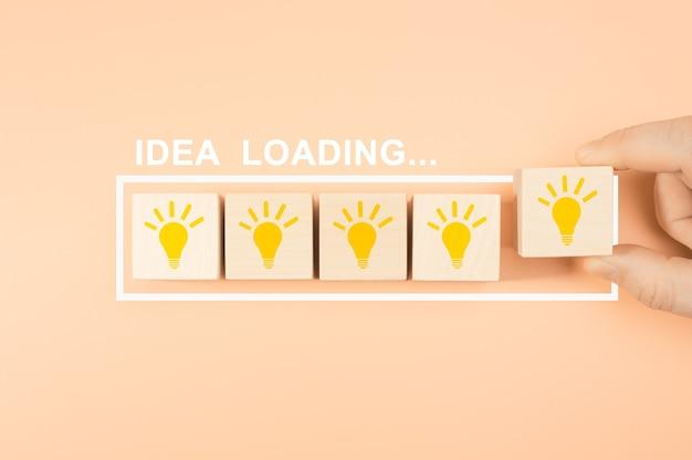 アイデアの読み込みの概念。電球で木製の立方体のブロック形状を手で置きます。手は光で木製の立方体ブロックを取ります。