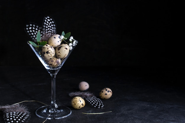 Idea of modern easter interior decoration.  quail eggs in cocktail glass on dark rusty background. copyspace for text