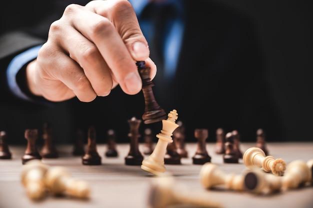 Идея победителя, делового лидерства и успешной концепции с шахматными фигурами и рукой бизнесмена