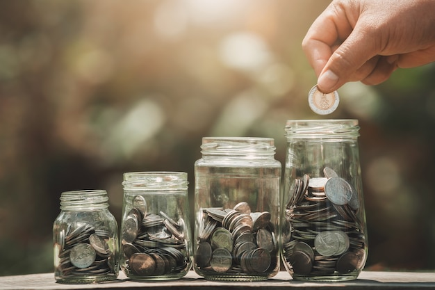 Idea saving money hand putting coins in to jug glass