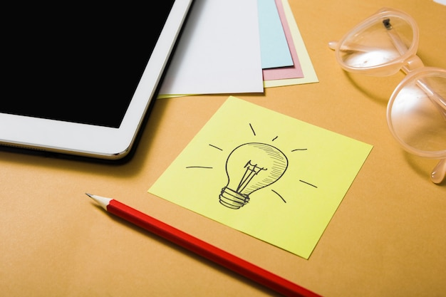 Idea symbol drawn with pencil and digital tablet on an orange backdrop