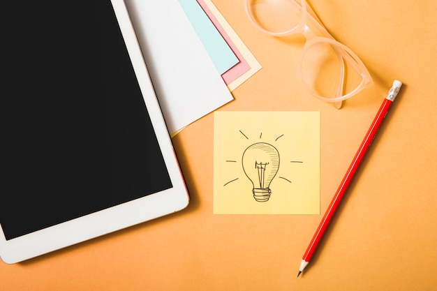 Idea symbol; pencil; eyeglasses; digital tablet and card paper on an orange backdrop