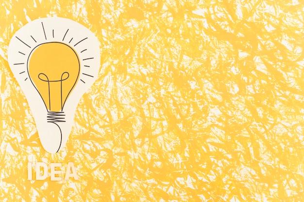 Текст идеи рядом с лампочкой, вырезанной на текстурированном фоне